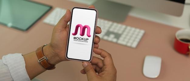 Beschnittener schuss des mannes, der modell-smartphone auf schreibtisch hält