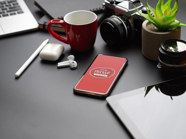 Beschnittener schuss des modell-smartphones auf schwarzem tisch mit tablette