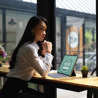Beschnittener schuss des nachdenklichen weiblichen büroangestellten, der mit dem falschen digitalen tablett sitzt