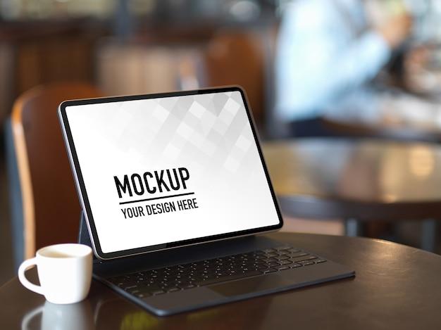 Beschnittener schuss des nachgebildeten digitalen tabletts mit tastatur und kaffeetasse auf kaffeetisch