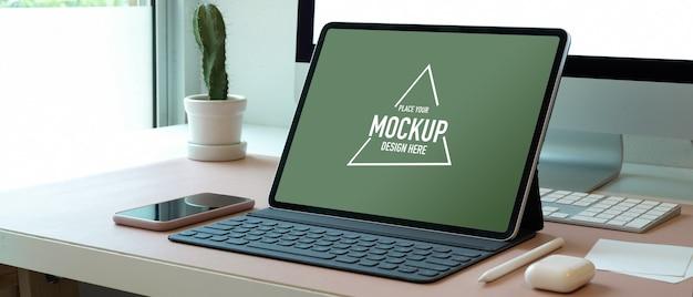 Beschnittener schuss des schein-digitalen tablets auf computertisch mit smartphone und zubehör im büro
