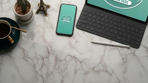 Beschnittener schuss von marmortisch mit mock-up-tablette, smartphone, kaffeetasse, dekorationen