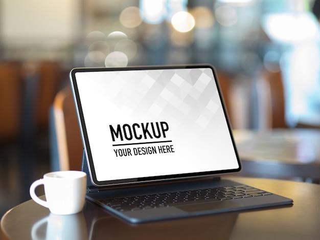 Beschnittener schuss von mock-up-tablette mit tastatur und kaffeetasse auf tisch in der cafeteria