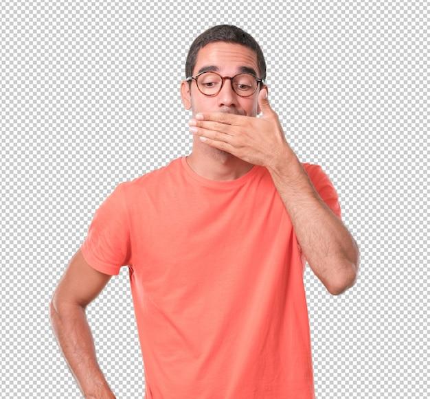 Besorgter junger mann, der seinen mund mit seiner hand bedeckt