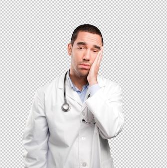 Betonter junger doktor mit einer geste der ehrlichkeit