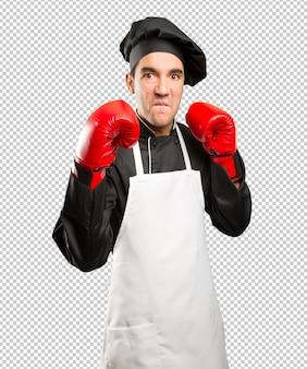 Betonter junger koch mit einem boxhandschuh