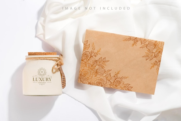 Bio duftende sojakerze mit etikett, bastelpapier und schatten auf weißem textil. modellverpackung
