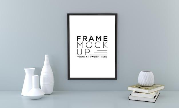 Blank frame mockup mit büchern und vasen auf grauer wand 3d-rendering