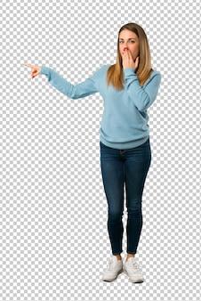 Blonde frau mit blauem hemd finger auf die seite mit einem überraschten gesicht zeigend