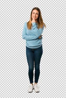 Blonde frau mit blauem hemd lächelnd und zur front mit überzeugtem gesicht schauend