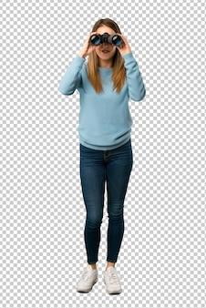 Blonde frau mit blauem hemd und im abstand mit ferngläsern schauen
