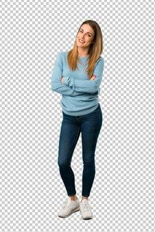 Blonde frau mit dem blauen hemd, das die arme gekreuzt in der vorderen position hält
