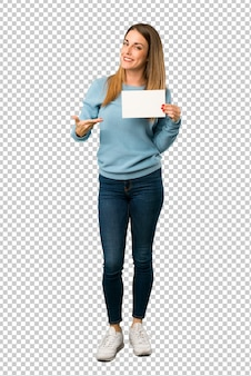 Blonde frau mit dem blauen hemd, das ein leeres plakat für einfügen ein konzept hält
