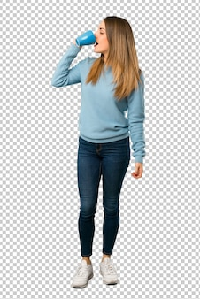 Blonde frau mit dem blauen hemd, das einen heißen tasse kaffee hält