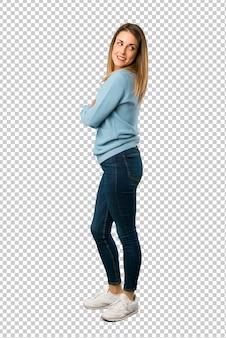 Blonde frau mit dem blauen hemd, das über der schulter mit einem lächeln schaut