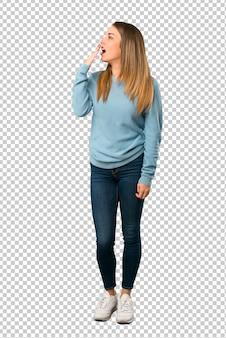 Blonde frau mit dem blauen hemd, das weit offenem mund mit der hand gähnt und bedeckt