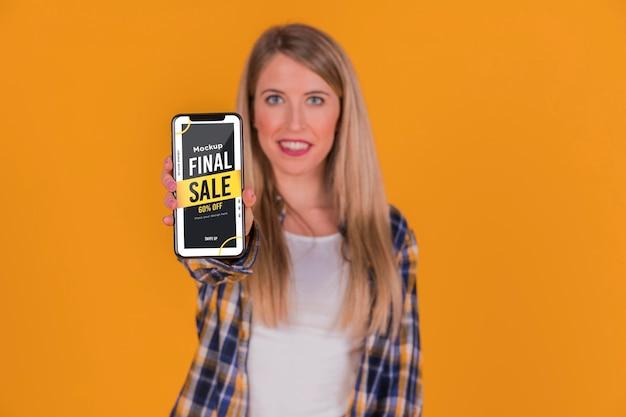 Blonde frau mit smartphone-konzept modell