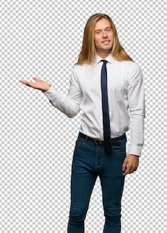 Blonder geschäftsmann mit dem langen haar, das eine idee beim schauen in richtung zu lächeln darstellt