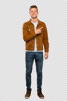 Blonder gutaussehender mann, der auf die seite zeigt, um ein produkt darzustellen