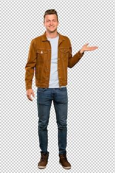 Blonder gutaussehender mann, der copyspace eingebildet auf der palme hält, um eine anzeige einzufügen