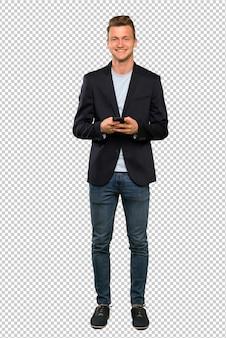 Blonder gutaussehender mann, der eine mitteilung mit dem mobile sendet