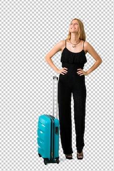 Blondes mädchen, das mit ihrem koffer aufwirft mit den armen an der hüfte reist