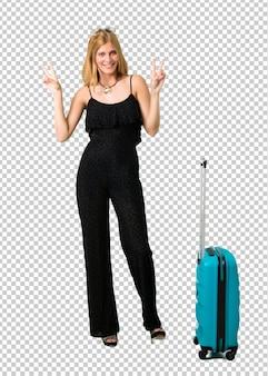 Blondes mädchen, das mit ihrem koffer lächelt und siegeszeichen zeigt