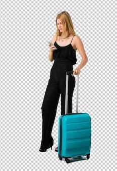 Blondes mädchen, das mit ihrem koffer reist, der eine mitteilung oder eine e-mail mit dem mobile sendet