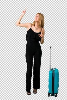 Blondes mädchen, das mit ihrem koffer reist, der mit dem zeigefinger eine großartige idee zeigt und oben schaut