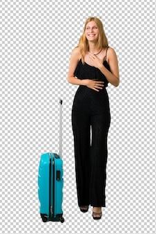 Blondes mädchen, das mit ihrem koffer viel lächelt, während hände auf kasten gesetzt werden