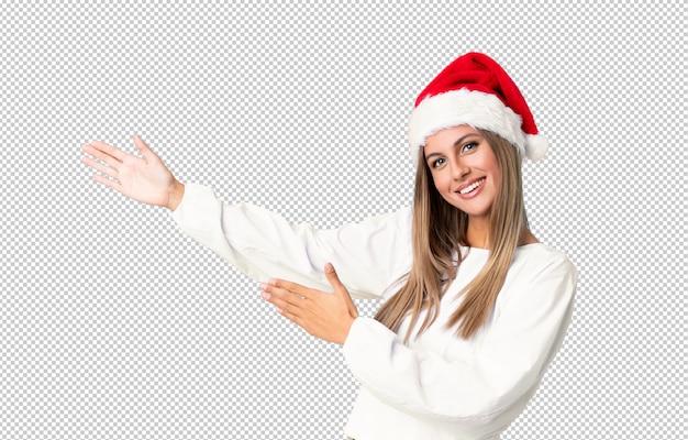 Blondes mädchen mit dem weihnachtshut, der hände zur seite für die einladung ausdehnt, um zu kommen