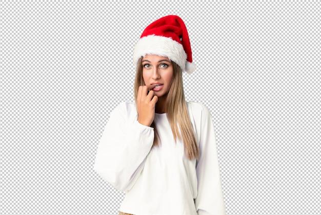 Blondes mädchen mit dem weihnachtshut nervös und erschrocken