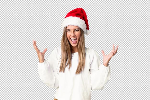 Blondes mädchen mit dem weihnachtshut unglücklich und mit etwas frustriert