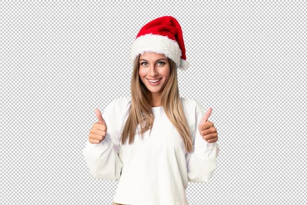 Blondes mädchen mit dem weihnachtshutgeben daumen up geste