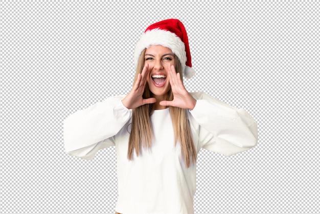 Blondes mädchen mit weihnachtshut schreiend mit weit offenem mund