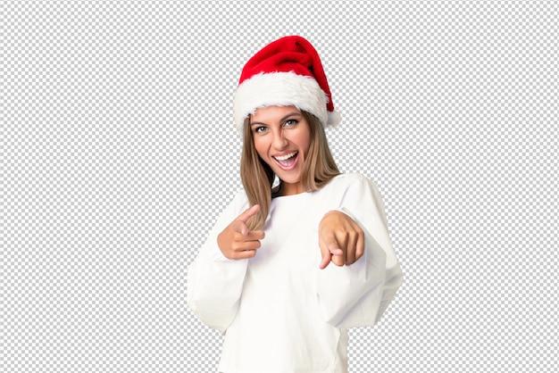 Blondes mädchen mit weihnachtshut zeigt finger auf sie