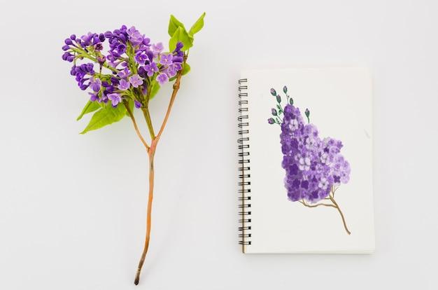 Blume mit realistischer farbe auf notizbuch
