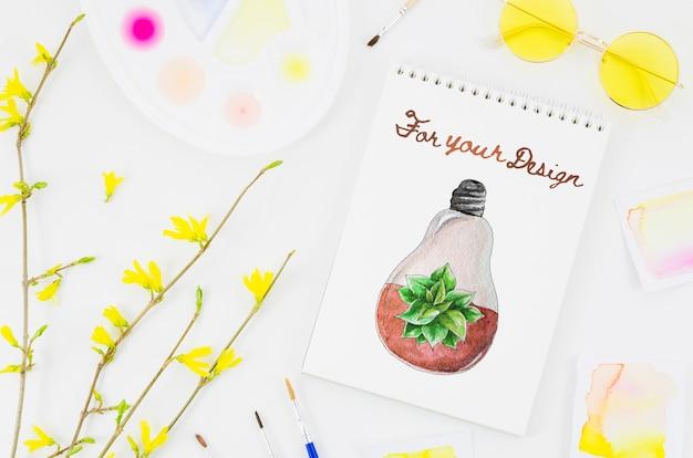Blumen nahe bei notizbuch mit künstlerischem abgehobenem betrag