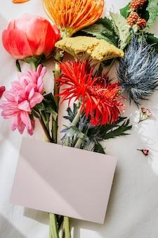 Blumenstrauß aus bunten blumen auf einem weißen bettlaken mit einem kartenmodell