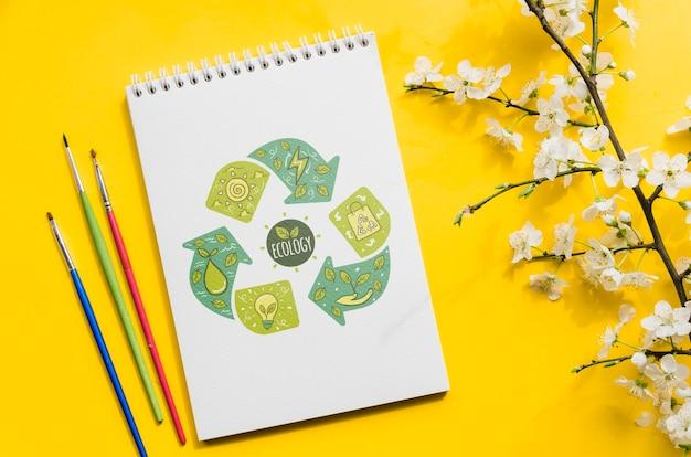 Blumenzweig und notizbuch mit abgehobenem betrag