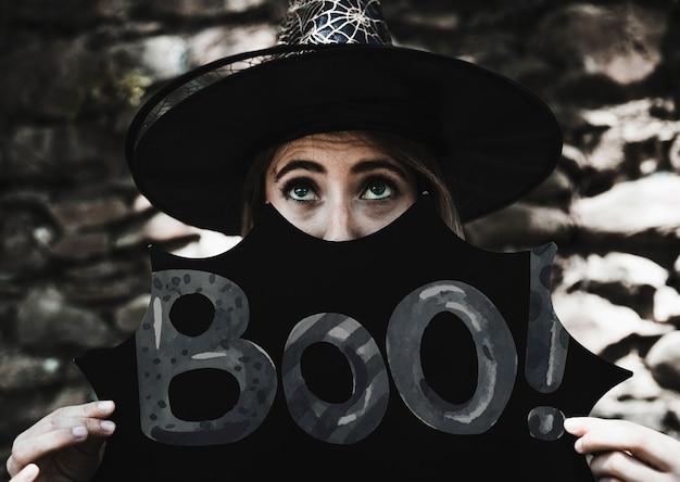 Boo! schild mit frau als hexe verkleidet