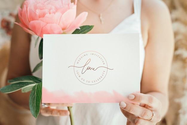 Braut, die ein weißes hochzeitskartenmodell hält