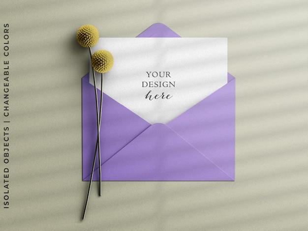 Briefpapiereinladungsumschlag mit grußpostkartenmodell-szenenschöpfer mit blumenflachlage