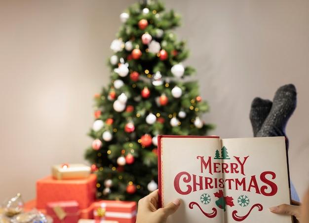 Buch der frohen weihnachten mit unscharfem weihnachtsbaum