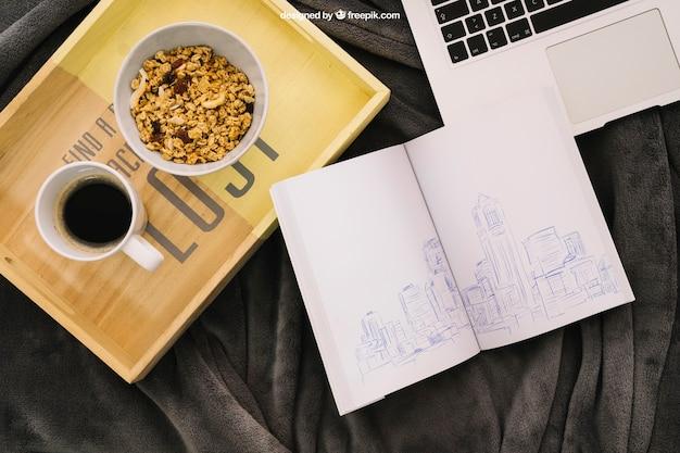 Buchaufbau mit kaffee, müsli und laptop