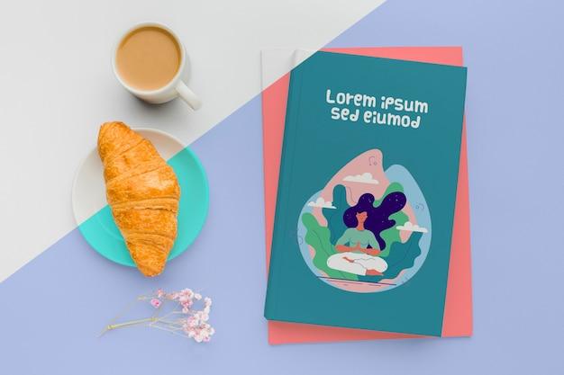 Buchdeckel-mock-up-arrangement mit tasse kaffee und croissant