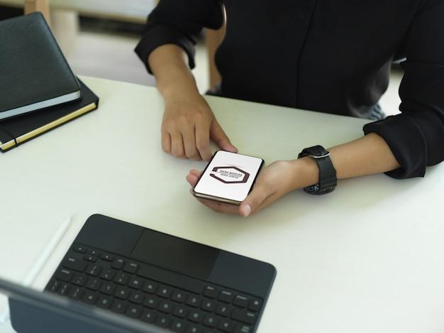 Büroangestellter, der modell-smartphone auf arbeitstisch verwendet