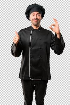 Chefmann in der schwarzen uniform, die ein okayzeichen mit den fingern zeigt und einen daumen aufgibt
