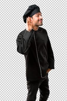 Chefmann in der schwarzen uniform hörend auf etwas, indem er hand auf das ohr setzt