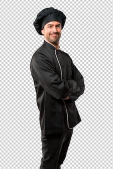 Chefmann in schwarzer uniform, die arme beim lächeln in seitlicher position gekreuzt